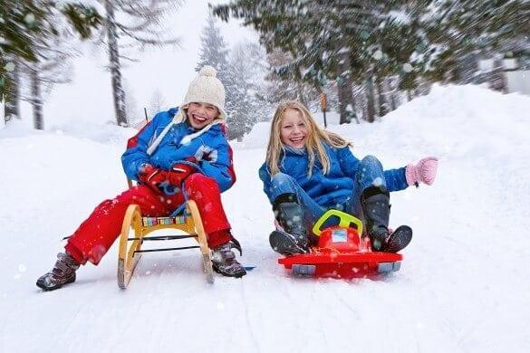 Mädchen rodeln im Schnee