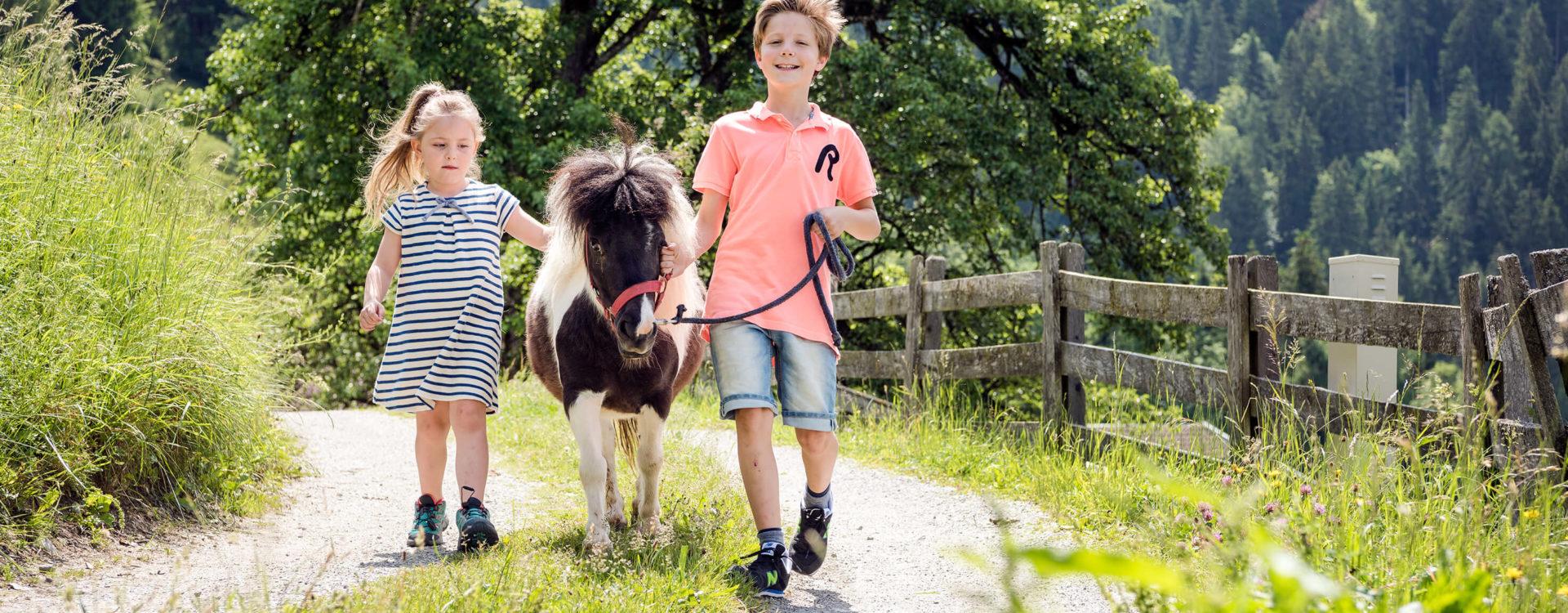 Pony spaziert mit Kindern
