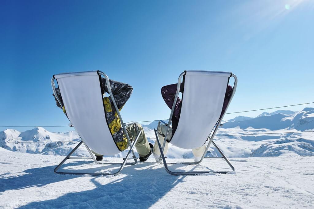 Skifahrer in Liegestühlen